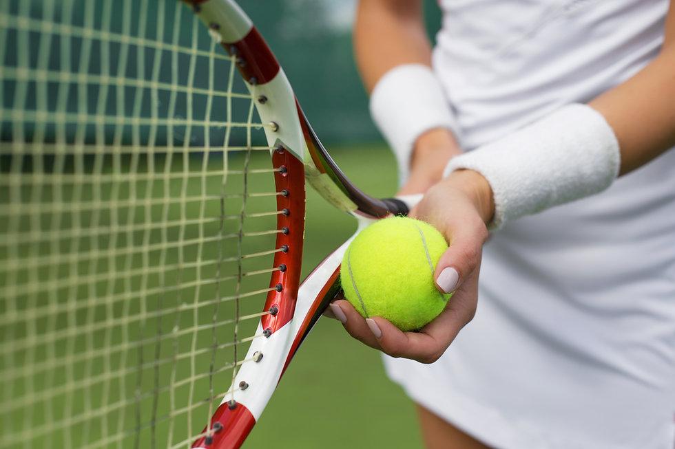 Sosteniendo la pelota y la raqueta
