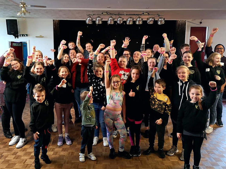 A picture of the SATS members in the rehearsal room all holding our arms up showing our Pink Sisters