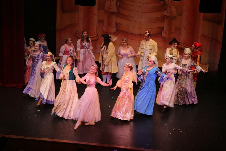 A group of SATS members dancing on stage in one of our past pantomimes