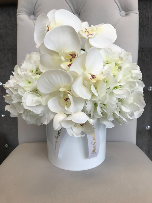 WHITE CYLINDER WITH WHITE HYDRANGEAS AND ORCHID