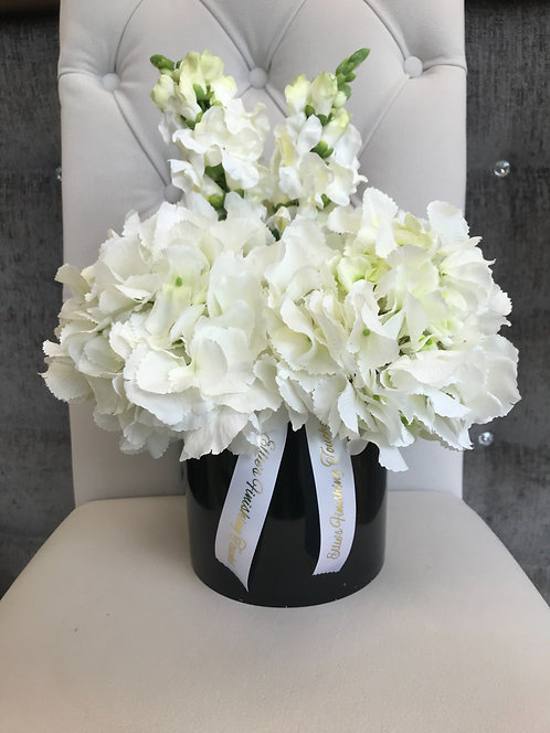 BLACK CYLINDER WITH WHITE HYDRANGEAS AND STOCKS