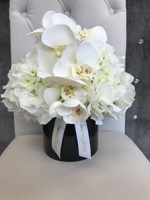 BLACK CYLINDER WITH WHITE HYDRANGEAS AND ORCHID