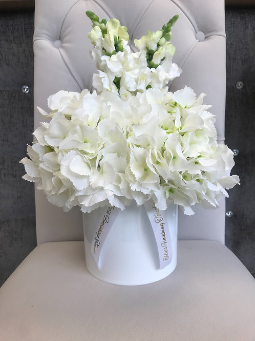 WHITE CYLINDER WITH WHITE HYDRANGEAS AND STOCKS