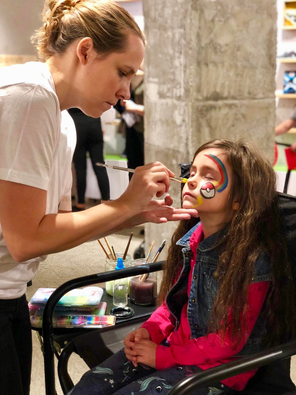 Face painter is drawing Pokémon's form to the kid, in Event Barcelona