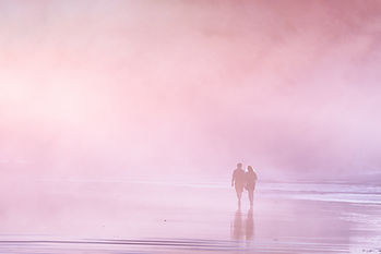 Couple walking in the beach at the sunse