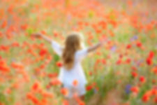 little girl wearing white dress raises h