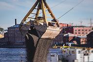 Bulk-handling crane unloading sand, road
