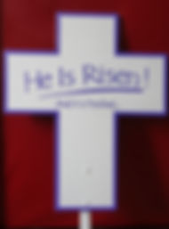 "E22- He Is Risen Cross trimed in purple with hand painted lettering. On an 18"" stake. 25""x21"""