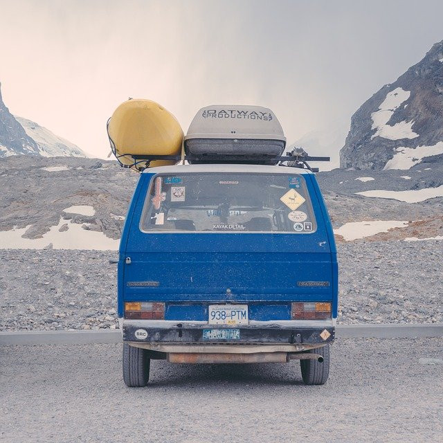 A blue vintage minivan with a roof rack and a canoe and storage box attached. Parked in from of some snowy hills