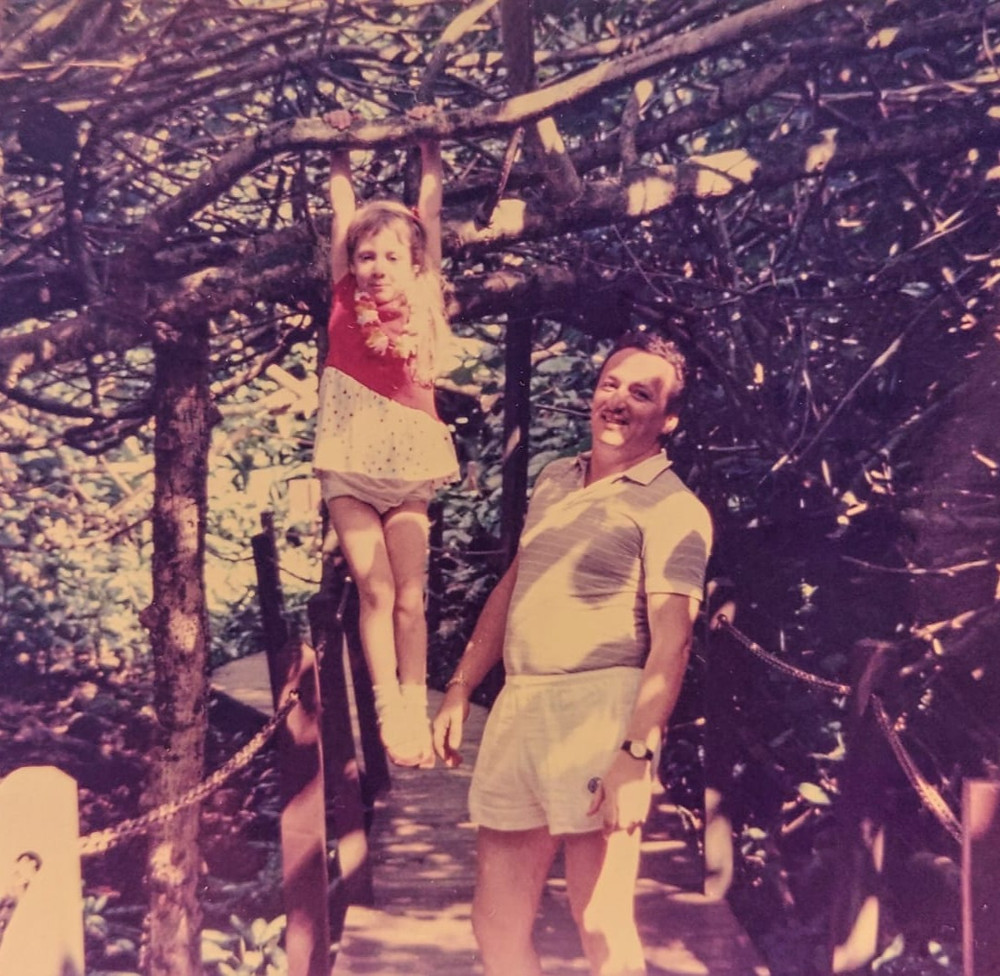 from 35 years ago, I'm hanging from a branch and my dad and standing and smiling next to me