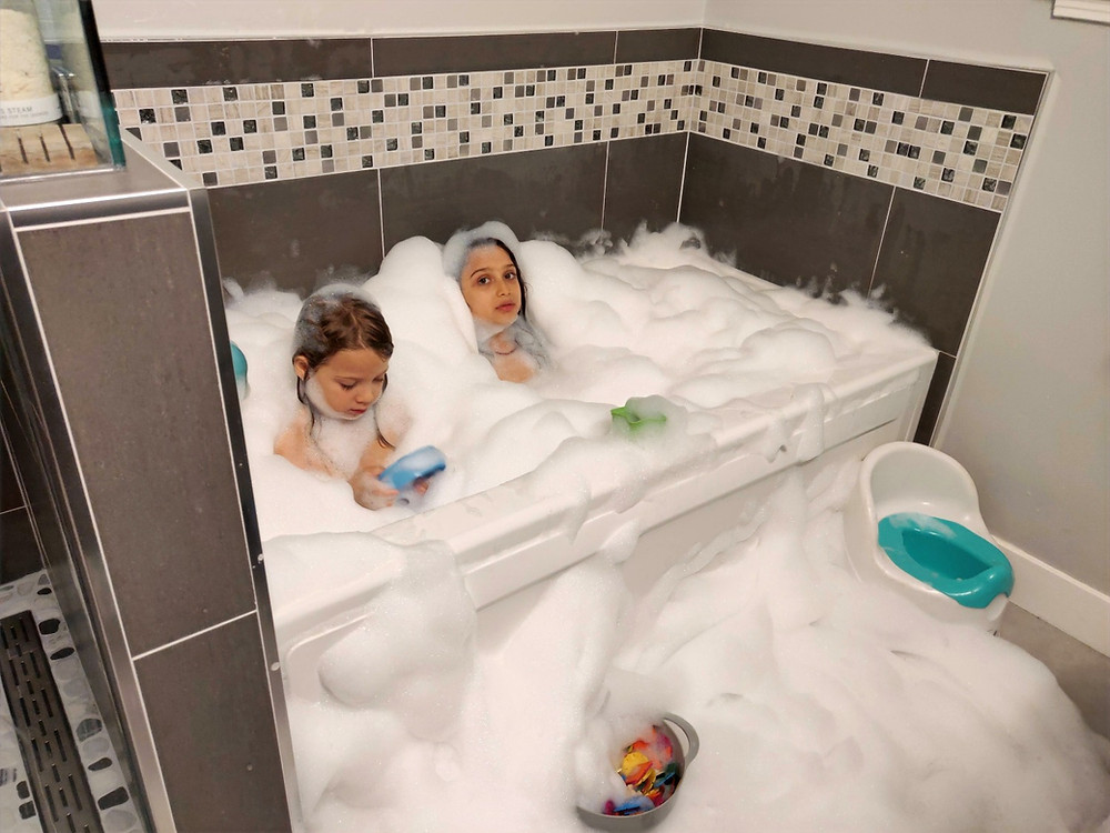 Leila and Dante in the bath with overflowing bubbles that spread onto the whole bathroom floor with worried expressions on their faces