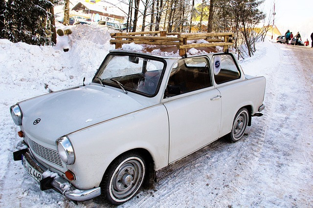a vintage car with a wooden rustic roof rack installed on top in a snowy area