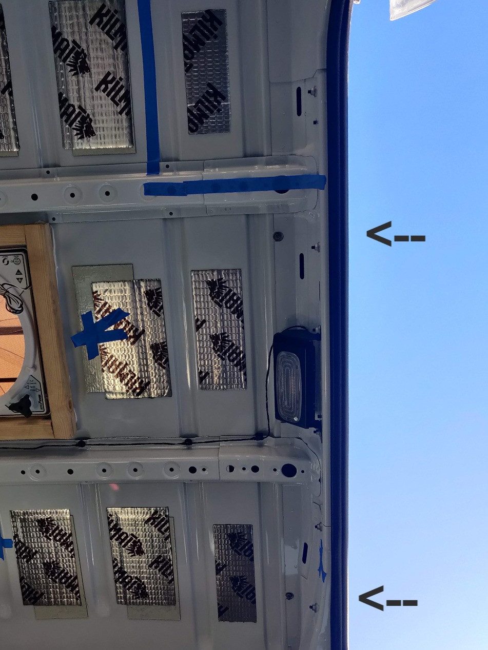 a zoomed out view of the inside of the van roof, with arrows pointing to the place where the screws are screwed in on the inside