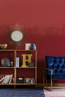 Mirror on red wall above gold shelves, n
