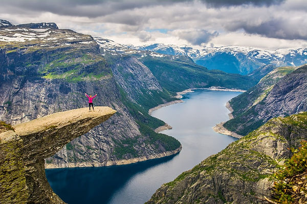 A woman standing on top of a ledge with her arms spread out wide above a fjord in Norway.