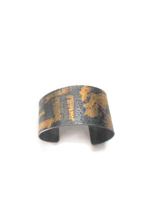 Asymmetrical silver and gold cuff bracelet.