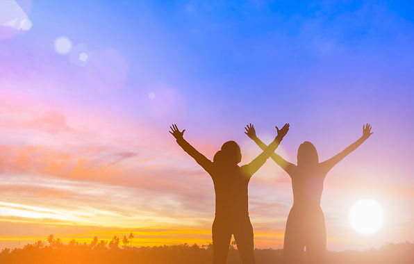 Two women with atop a mountain during sunrise with their hands in the air unleashing leadership.