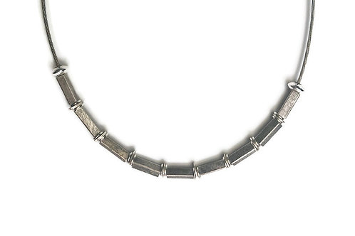 This necklace features oxidized sterling silver square tubes, sterling silver disks and rings.