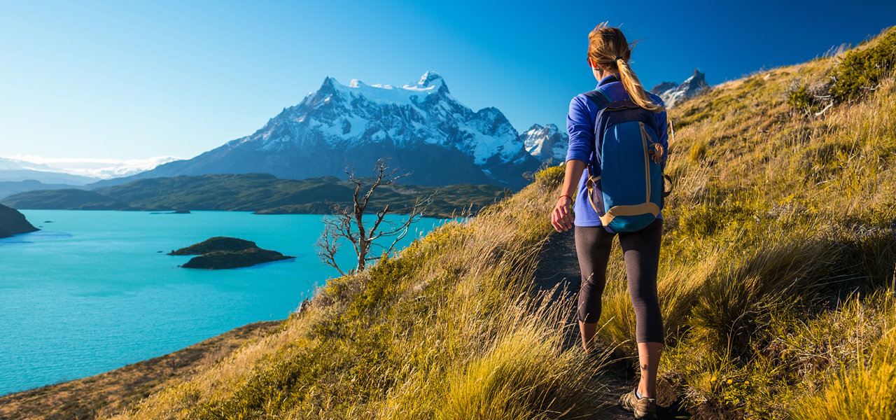 woman-hiking-lake-mountains-summit-leade