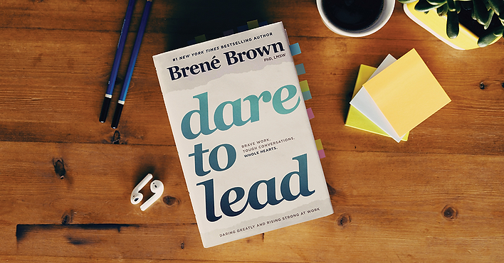 Dare to Lead Book written by Brene Brown placed on a table with headphones, post its, coffee and a pens.