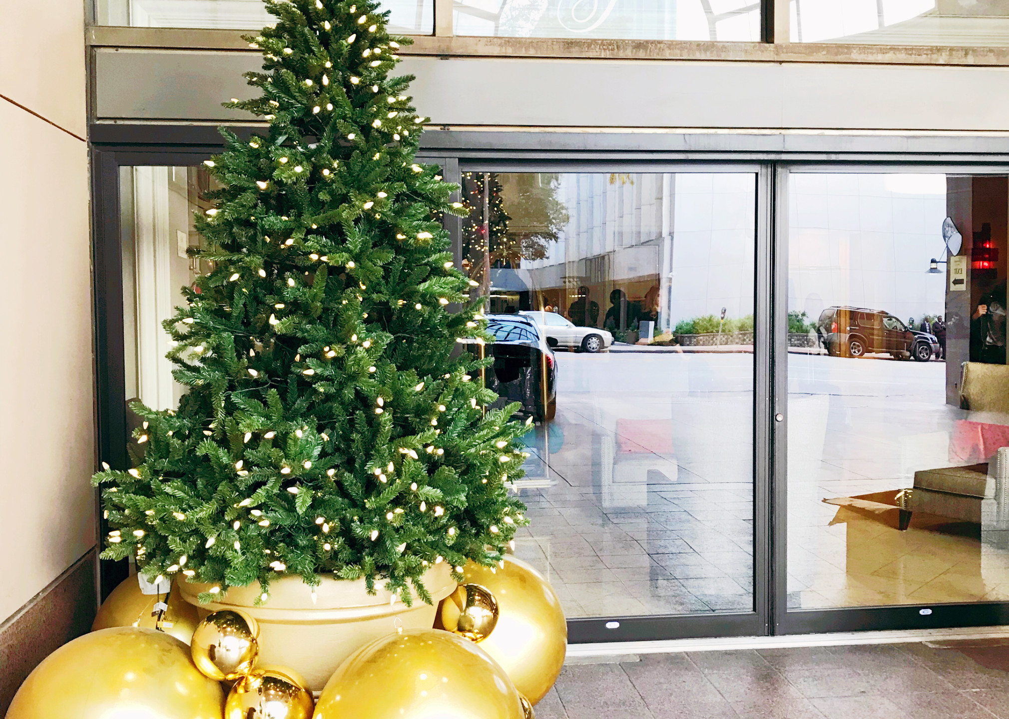 10 ft' Natural Christmas tree display designed by Franzie's Flower Design for the Fairmont Dallas hotel, located at valet.