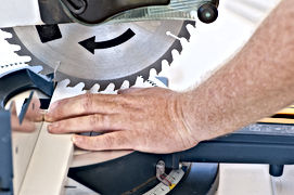 Workers hand under unprotected saw blade.
