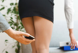 Man sexually harassing woman by taking photos under woman's skirt.