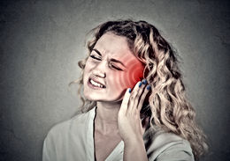 Woman holding ear from tinnitus and head from headache