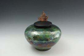 a green glazed ceramic vase with a black lid topped with a piece of copper