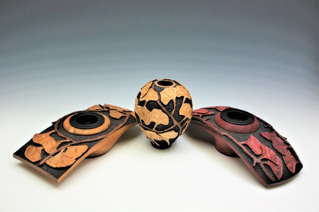 three ornate carved wooden vases with a ginko relief pattern carved and stained onto them
