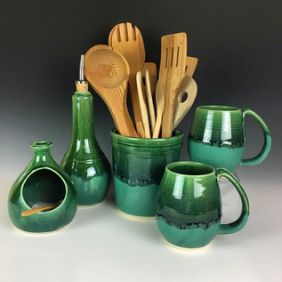 two mugs, a salt keeper, an oil jar, and a large cylindrical utensil holder, all handmade ceramic with a matching two-toned green glaze