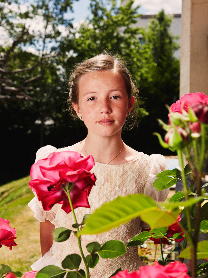 Retrato primera comunión niña en el jardin con flores