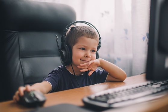 little boy with headset using computer,
