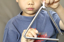Music-Appreciation-For-Young-Children-playing-the-triangle-instrument