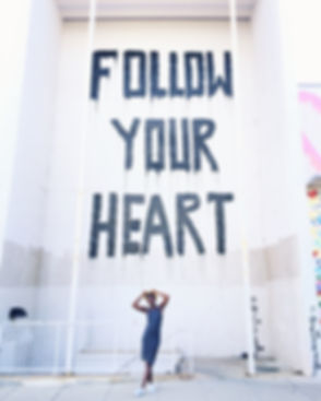 Black Women Entrepreneurs standing in front of a Mr. Brainwash Follow Your Heart Mural at Union Market Washinton DC