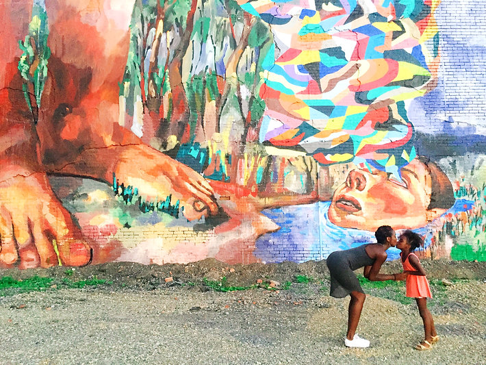 Black mother kissing her daughter in front of a mural