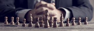 Retro style image of a businessman with clasped hands planning strategy with chess figures