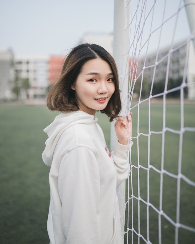 Female soccer player standing behind goal.