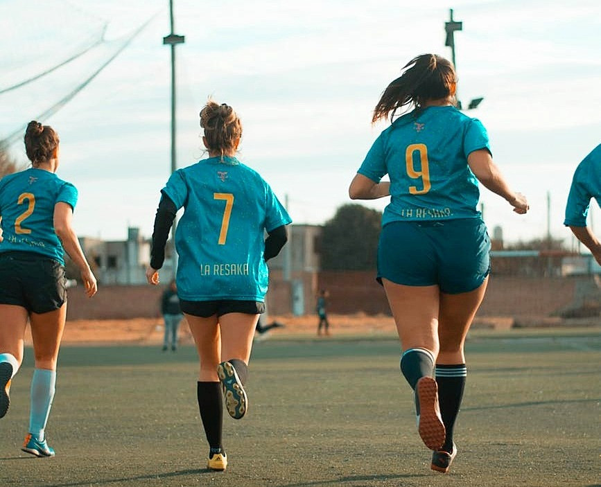Female soccer players running on field.