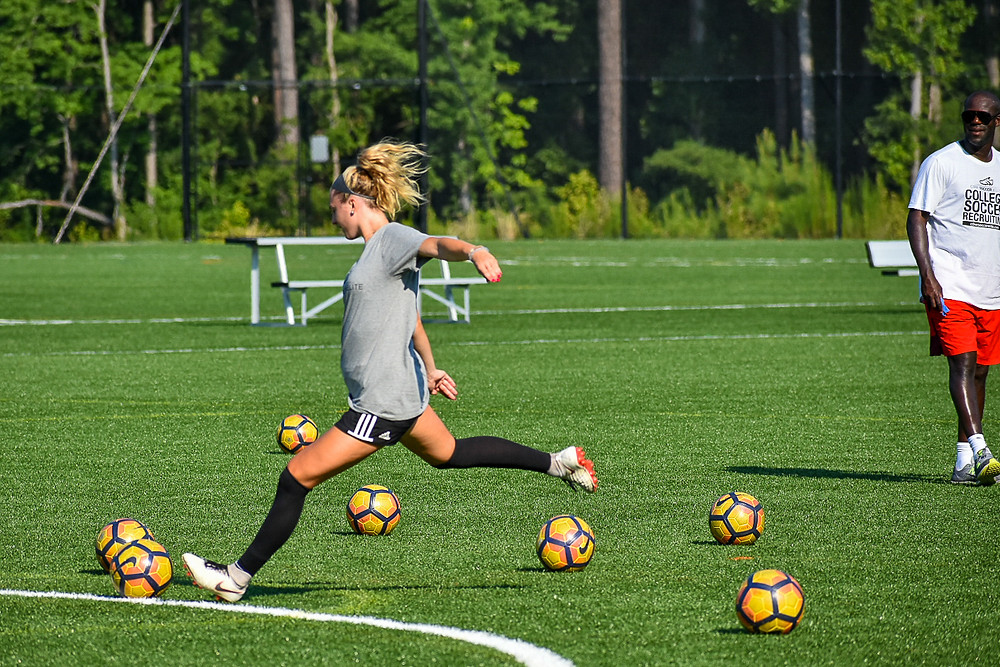 Female soccer player striking a ball during training session