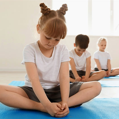 Children seated on mats in yoga meditation class