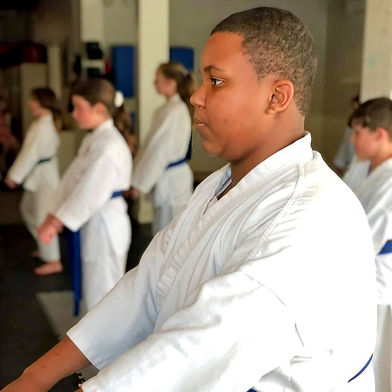 Boy wearing karate gi doing kata training in class