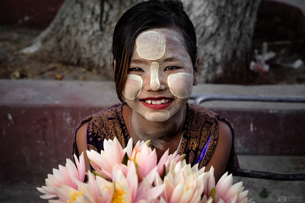 Burmese girl is smiling and selling flowers for donation in the Pagoda