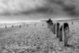 The decayed wooden sea defences stand on this windswept beach, much like ancient standing stones in a Neolithic landscape.