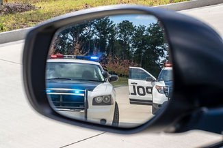 Two police vehicles stop a sedan on a ro