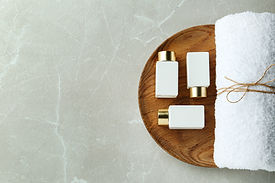 Top view of wooden tray with cosmetic bottles and towel on light grey marble table, space