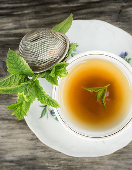Cup of tea with mint and tea strainer on