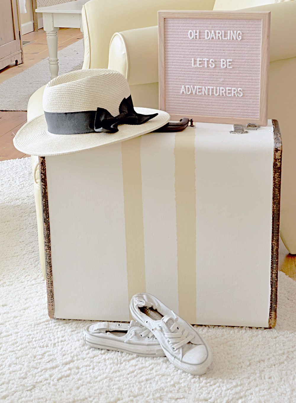 Vintage painted DIY suitcase with Pink letter board and hat and worn sneakers.