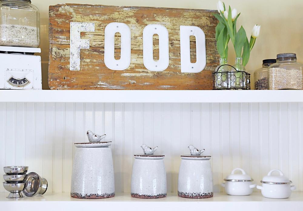 Vintage wooden FOOD sign on top kitchen shelf with other vintage decor.
