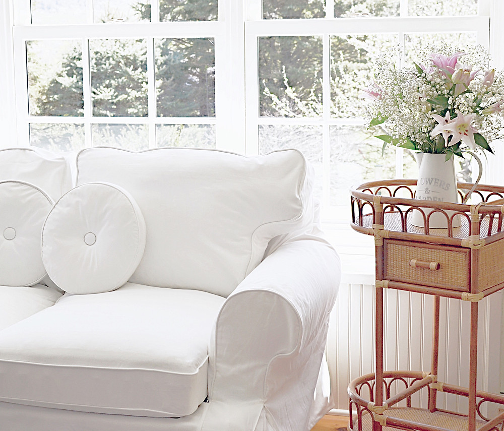 White loveseat with vintage wicker beverage cart with pink flowers.